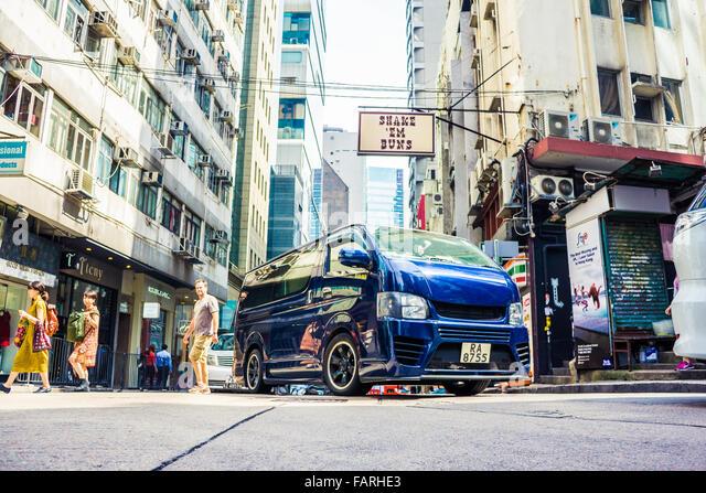 A busy Hong Kong street scene featuring a customized minivan - Stock Image