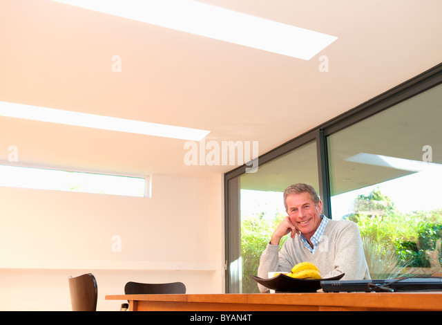 Happy business man at desk - Stock Image