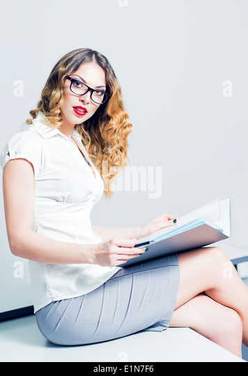A beautiful young business woman working with documents - Stock Image