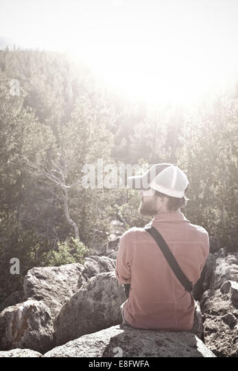 USA, Wyoming, Man sitting on rocks above trees - Stock Image