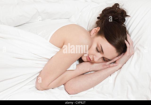 Beautiful brunette woman sleeping alone - Stock Image