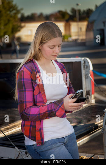 Teen girl using iPhone mobile device  outdoors hanging out while waiting. MR  © Myrleen Pearson - Stock-Bilder