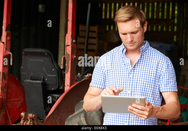 Farmer Holding Digital Tablet Standing In Barn With Old Fashioned Tractor - Stock Image