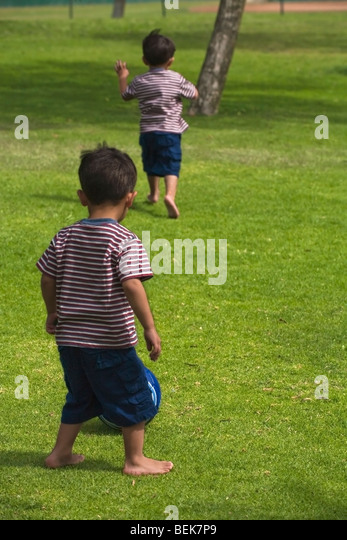 Two boys playing soccer in a park - Stock-Bilder