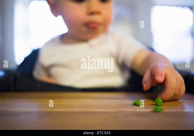 Toddler girl pointing at peas - Stock Image