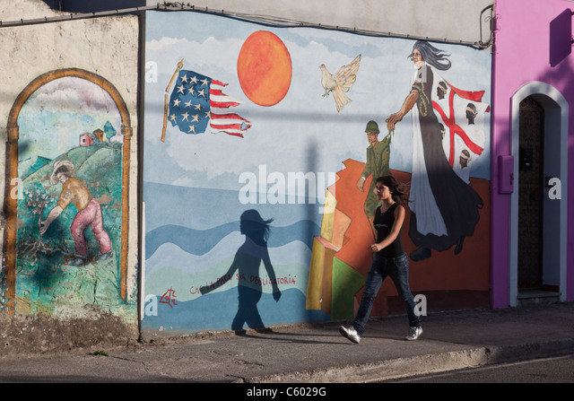 Street Scene with girl in background wall painting, Italy Sardinia - Stock Image