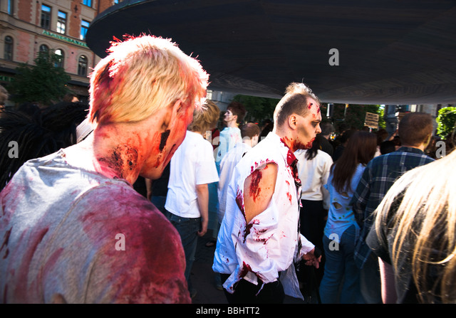 Bloody wounded male zombies at mushroom at Stureplan in Stockholm during horror zombie masquerade event Zombie Walk - Stock Image