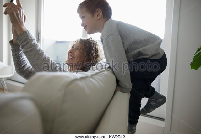 Playful mother and son taking selfie with digital tablet on sofa - Stock Image