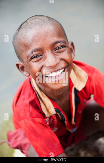 Smiling Indian street boy washing himself in a river in the Indian countryside - Stock Image
