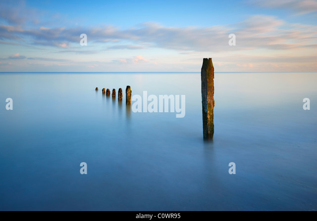 Long exposure and sea defences along the southern coastline at Winchelsea beach, East Sussex. - Stock Image