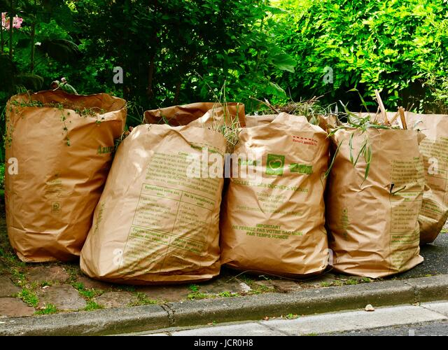 Paper sacks full or grass and yard clippings left at the curb for pick up. Auvers-sur-Oise, France. - Stock Image