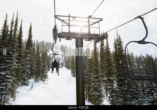 Man in ski lift, rear view - Stock Image