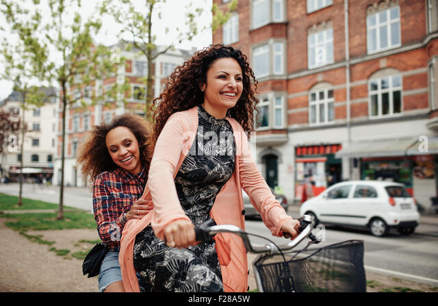 Portrait of cheerful young friends riding a bicycle in the city. Young girls outdoors enjoying bicycle ride on street. - Stock Image