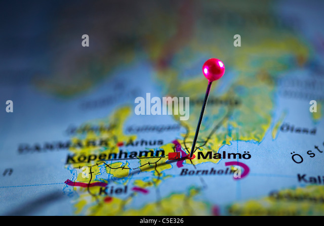 Close-up of a pink map pin on Malmo at a map - Stock Image