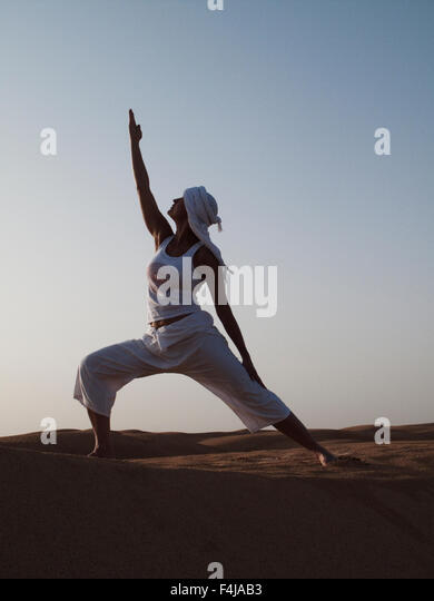 Woman performing yoga in the desert, Tunisia. - Stock Image