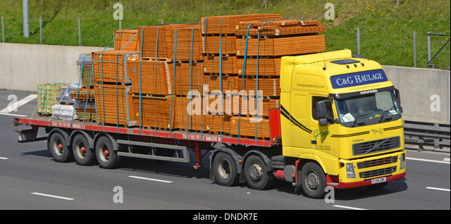 Haulage contractor truck and articulated trailer loaded with timber fencing panels - Stock Image