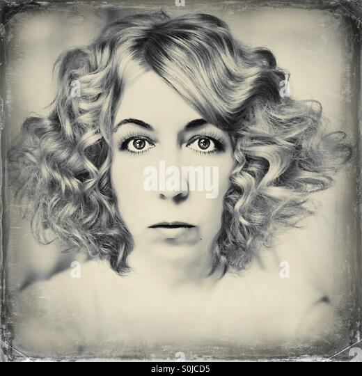 Wide eyed woman vintage looking photo - Stock Image
