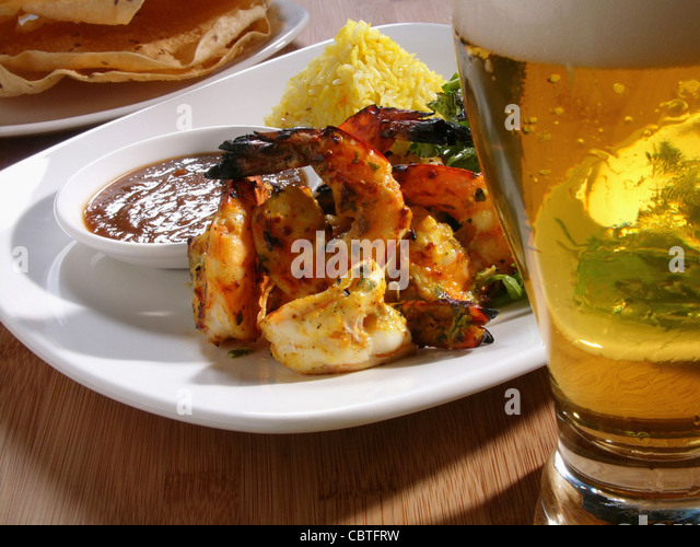 Shrimp entree and glass of beer - Stock Image