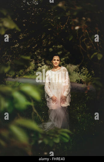 young woman wearing white dress standing in the forest - Stock Image