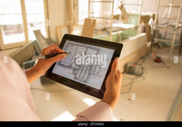Architect woman drawing with stylus on electronic tablet in Construction site - Stock Image