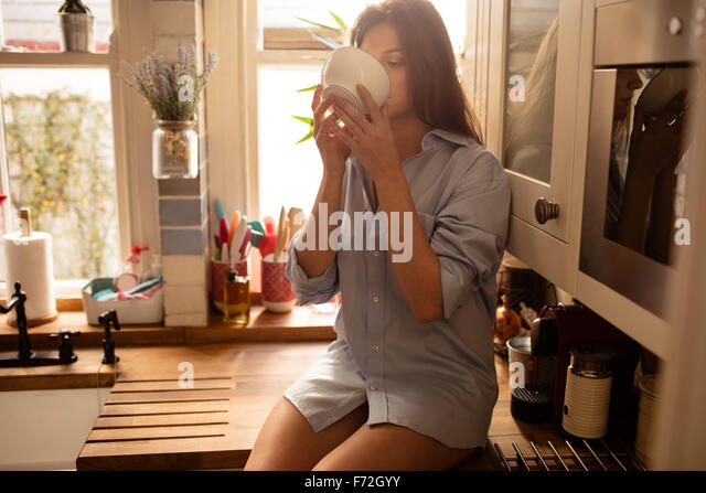 Young woman drinking by a mug - Stock Image