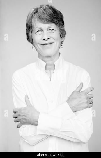 Black and white studio portrait of senior woman with arms folded - Stock Image