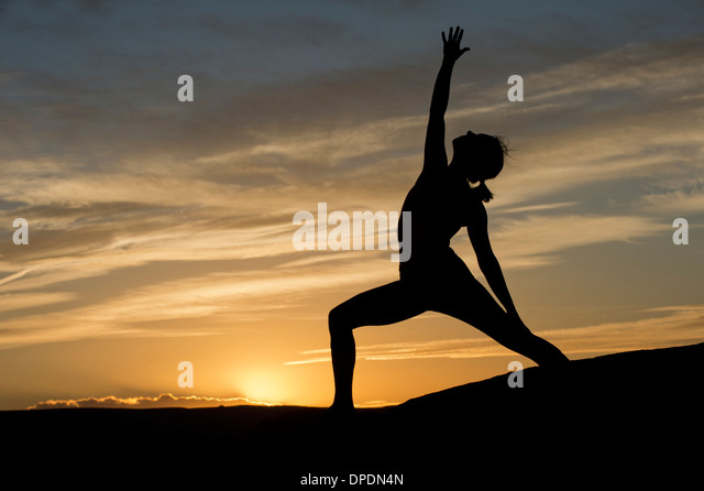 Silhouette of young woman doing yoga, Moab, Utah, USA - Stock Image