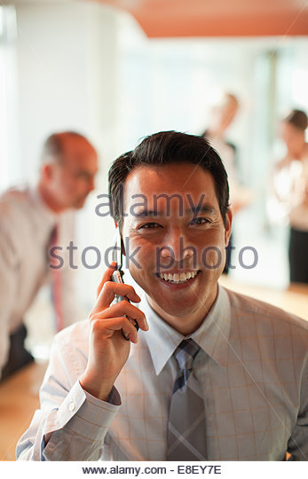 Businessman talking on cell phone in office - Stock-Bilder