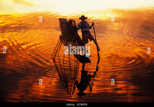 Intha fisherman rowing boat with legs and fishing at sunset Inle Lake Myanmar - Stock-Bilder