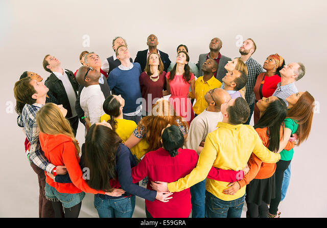 Business people forming circle and looking up - Stock Image