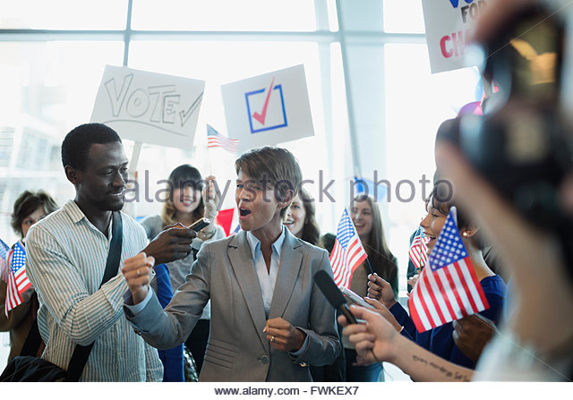 Cheering female politician being interviewed at political rally - Stock Image