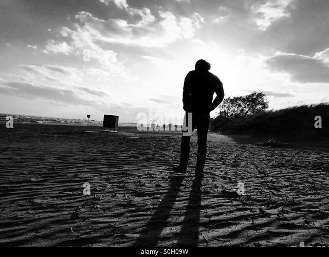 A man walking on a beach - Stock Image