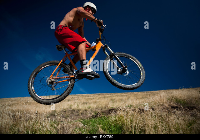 A male mountain biker gets air while riding a trail on Mt. Sentinel, Missoula, Montana. - Stock Image