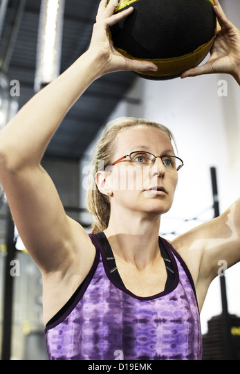 Woman holding medicine ball above her head - Stock Image