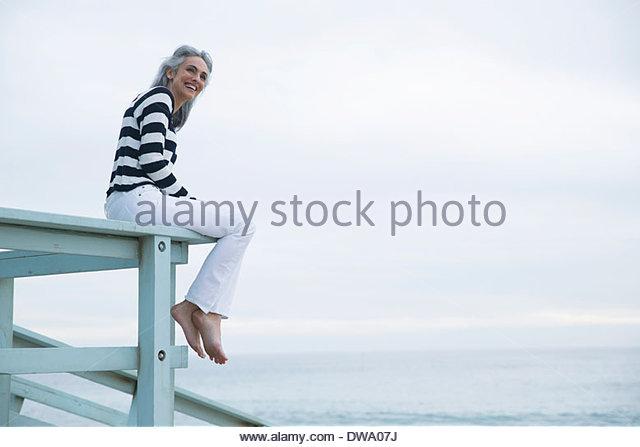 Mature woman sitting on beach house balcony, Los Angeles, California, USA - Stock Image
