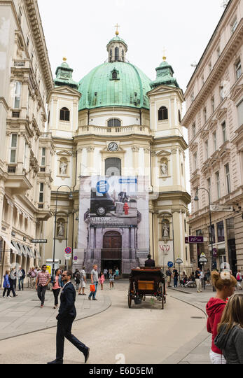 Peterskirche (English: St. Peter's Church), Vienna with an ad poster over entrance and a horse coatch - Stock Image