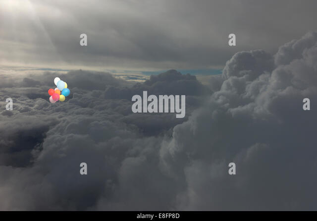 Group of colorful balloons floating high in sky above clouds - Stock-Bilder