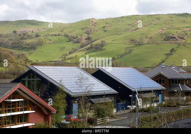 Roofs tiled with photovoltaic solar energy panels in Dyfi Eco Park, Machynlleth, Wales. - Stock Image