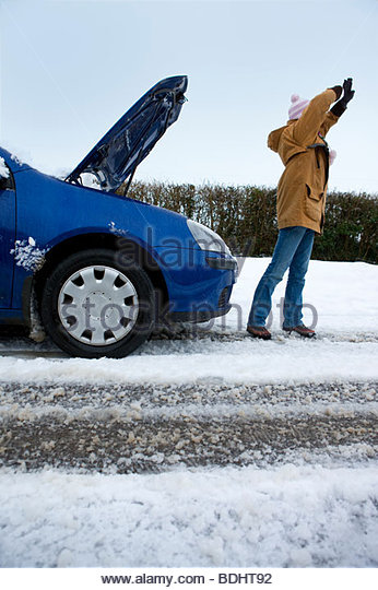 Stranded woman flagging down car in snow - Stock Image