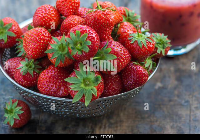 Fresh strawberries in a bowl on wooden table - Stock-Bilder
