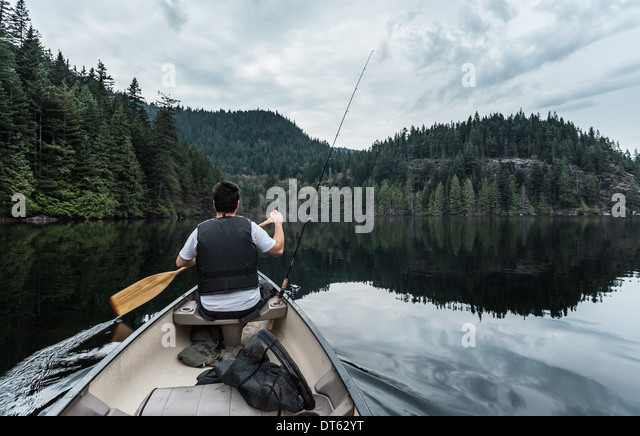 Young man fishing, Buntzen Lake, British Columbia, Canada - Stock Image