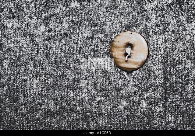 Close Up Of Grey Sweater And Button - Stock Image