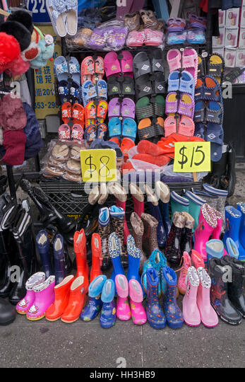 Inexpensive shoes slippers & boots for sale at a bargain shop on Main St. in Chinatown, downtown Flushing, Queens, - Stock Image