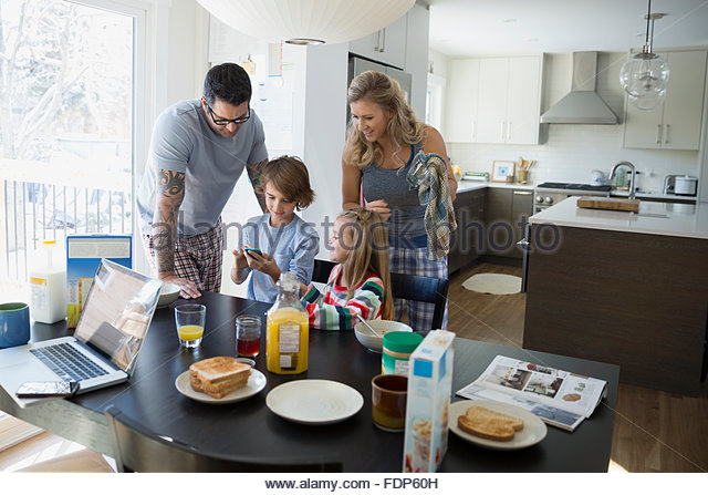 Family looking at cell phone at breakfast table - Stock-Bilder