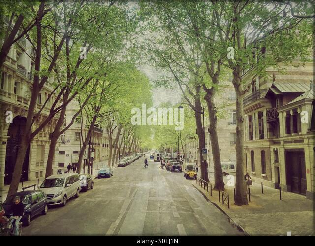 Typical Parisian neighborhood with tree-lined streets, old buildings with classical architecture, parked cars, people - Stock Image