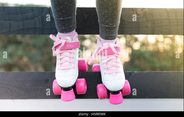 A little girl sitting on a fence in roller skates - Stock Image