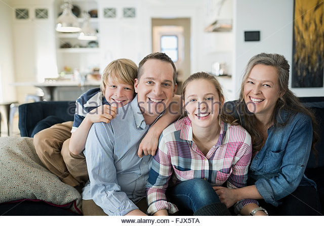 Portrait smiling family on living room sofa - Stock Image