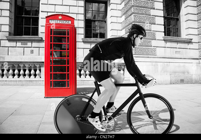 Cyclist cycling past red telephone box - Stock-Bilder