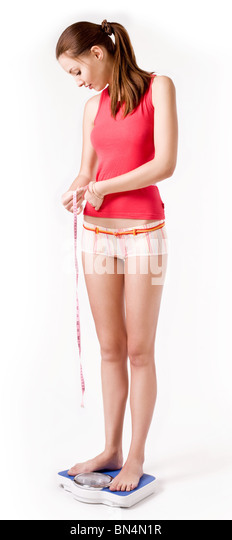 Girl on scales measuring her waist - Stock Image