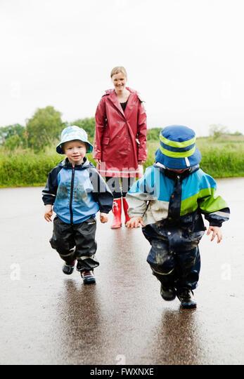 Sweden, Skane, Arild, Mother and daughters (2-3, 4-5) walking on wet road - Stock Image